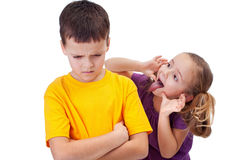 Young girl mocking boy - isolated. Young girl mocking angry boy - isolated Royalty Free Stock Photography