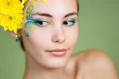 Young girl model with fantasy makeup and flowers. Young girl model with fantasy makeup and chrysanthemum flowers in her hair Stock Photo