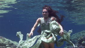 Young girl model underwater poses for camera on background of corals in Red Sea. Filming a movie. Extreme sport in marine landscape, coral reefs, ocean stock video footage