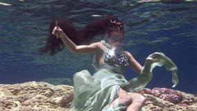 Young girl model underwater poses for camera on background of corals in Red Sea. Filming a movie. Extreme sport in marine landscape, coral reefs, ocean stock video