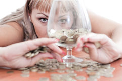 A young girl, money, and a glass goblet Stock Photos