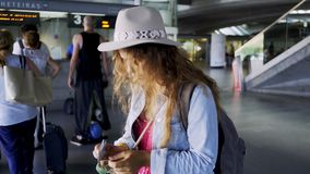 Young girl with money in hands near ticket office. Young famale passenger counting money near ticket office at blurred background inside modern railway station stock footage