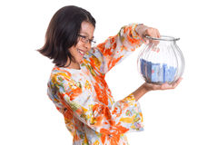 Young Girl With Money Jar VII. Young asian girl with money jar over white background stock photo