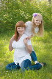 A young girl with mother on a green grass Royalty Free Stock Photography