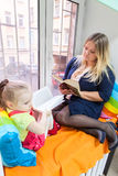 Young girl with mother read books and sitting on windowsill Stock Photo
