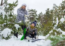 Young girl, mother, walking with her little son in the winter forest. Winter Games. snow woman. sledge. snowballs Royalty Free Stock Photo