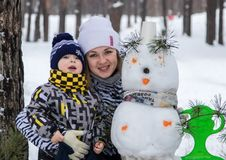 Young girl, mother, walking with her little son in the winter forest. Winter Games. snow woman. sledge. snowballs Stock Photography