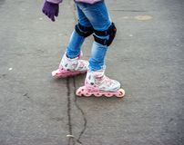 Young girl in motion on rollerblading. Young girl in motion on roller skates with protection on the knees in park and special track for ride Stock Photography
