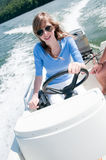 Young girl on motorboat. Beautiful young girl driving motorboat royalty free stock images