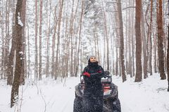 young girl on a motorcycle rides in snow-covered pine forest in royalty free stock image