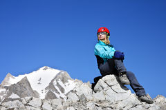 Young girl in the mountain. Young girl siting on the rock high in the mountains Royalty Free Stock Images