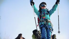 A young girl mountain climber rejoices at the peak. she smiles happily and waves her ski poles. A young girl mountain climber rejoices at the peak. she smiles stock footage
