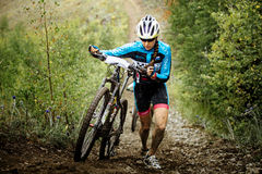 Young girl mountainbiker climb mountain on foot with their bikes Stock Photos