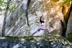 Young girl in mountains doing yoga exercise outdoor. stock images