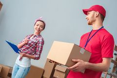 Young girl moving to new place standing checking order from delivery man holding box stock photos