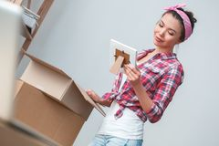 Young girl moving to new place standing packing things looking at photo smiling nostalgic stock photography