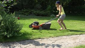 Young girl mowing green grass lawn with orange push mower. 4K stock video