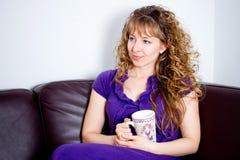 Young girl with mug on brown sofa Stock Photos