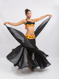 Young girl mulatto dancing in a long black dress candid Stock Images