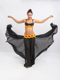 Young girl mulatto dancing in a long black dress candid Royalty Free Stock Images