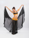 Young girl mulatto dancing in a long black dress candid. Young girl mulatto dancing in a long black candid open dress, is isolated on a light background Royalty Free Stock Photography