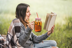 Young girl in nature with a drink in hand reading a book Stock Photography
