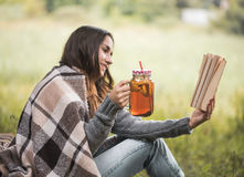 Young girl in nature with a drink in hand reading a book Royalty Free Stock Photos