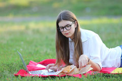 Young girl on the nature of eating fast food and working at a laptop Stock Images