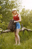Young girl on nature with hat and backpack. Summer Royalty Free Stock Photography