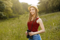Young girl on nature with hat and binocular. Summer Royalty Free Stock Photo