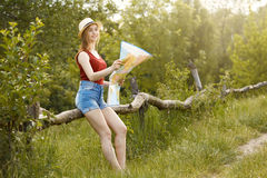Young girl on nature with hat and map. Summer Stock Photography