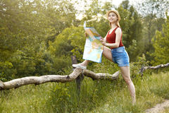 Young girl on nature with hat and map. Summer Stock Photo