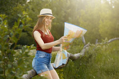 Young girl on nature with hat and map. Summer Stock Images