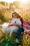 Young girl in a nature park hugging a white dog Samoyed Laika at sunset. 1 Royalty Free Stock Image