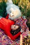 Young girl in a nature park hugging a white dog Samoyed Laika at sunset. 1 Stock Photography