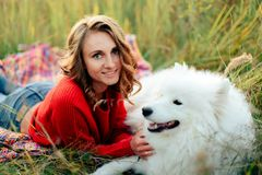 Young girl in a nature park hugging a white dog Samoyed Laika at sunset. 1 Royalty Free Stock Images