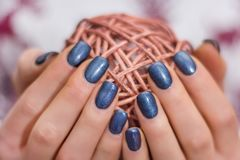 Female with navy blue nails polish holding decorative hank. Young girl with navy blue nails polish holding decorative hank. Manicure concept image. Close up royalty free stock photography
