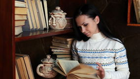 The young girl near a bookshelf reading a book stock video