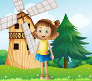 A young girl near the farmhouse with a windmill Royalty Free Stock Photo