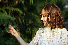 Young girl near fir. Young girl with curly hair near fir Royalty Free Stock Photography
