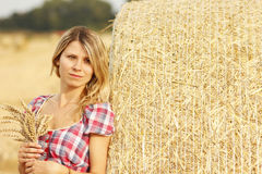 Young girl near haystacks Royalty Free Stock Photos