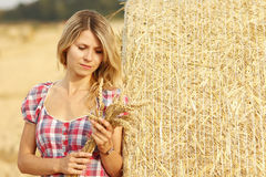 Young girl near haystacks Royalty Free Stock Photography
