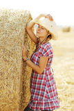 Young girl near haystacks in cowboy hat Royalty Free Stock Image