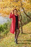 A girl near a river and a tree with yellow leaves in a red coat and a black dress adjusts her hair royalty free stock image