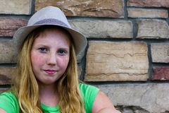 Young girl near a rock wall. An adolescent girl wears a hat while smiling Royalty Free Stock Images