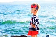 Young girl near the sea rock Stock Photos