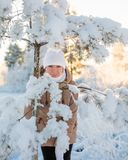 Young girl near snowy spruce Stock Images