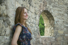 Young  girl near a stone wall Stock Photo