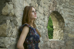 Young  girl near a stone wall Stock Photography