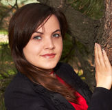 Young girl near the tree. Young girl in a black jacket near the tree Royalty Free Stock Photo